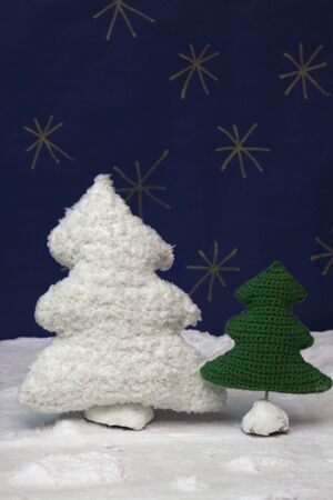snowed: a vertical frontal view of some crochet trees in a snowed set with space for a message Stock Photo