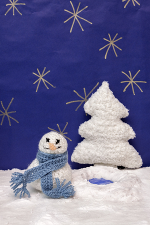 snowed: a horizontal frontal view of a crochet snowman and tree in a snowed set with space for a message Stock Photo