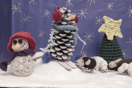 snowed: a horizontal frontal view of a boy  and crochet snowman, skier, sheep and tree in a snowed set with space for a message