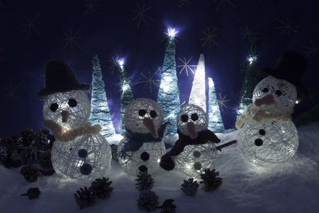 snowed: a horizontal frontal view of some handmade illuminated snowmen and trees in a snowed scene with space for a message Stock Photo