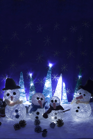 snowed: a vertical frontal view of some handmade illuminated snowmen and trees in a snowed scene with space for a message Stock Photo
