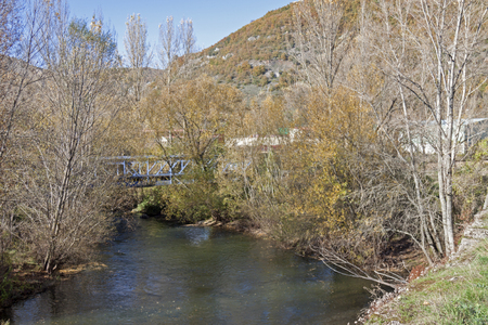 a horizontal frontal view of a river with a train bridge at the background, Pola de Gordon, Leon, Spain Standard-Bild