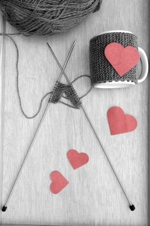 warmer: a vertical overhead view of the creation of a romantic mug warmer in black and white with red hearts Stock Photo