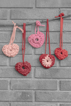 b w: a vertical frontal view of some hearts hanging on a branch over a brick background with space for a message back and white with color hearts