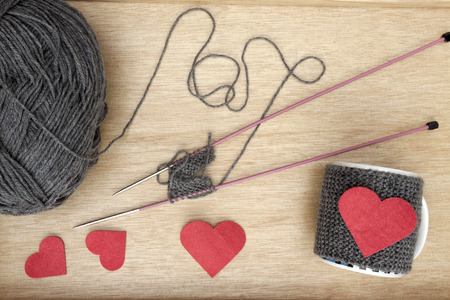 warmer: a horizontal overhead view of the process of knitting a romantic mug warmer and some of the tools needed Stock Photo