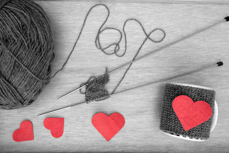 warmer: a horizontal overhead view of the process of knitting a romantic mug warmer and some of the tools needed in black and white with a red hearts Stock Photo