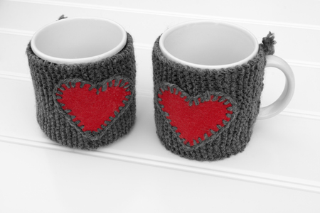 warmer: a horizontal frontal view of two mug with a warmer with a heart on a white table with space for a message Stock Photo