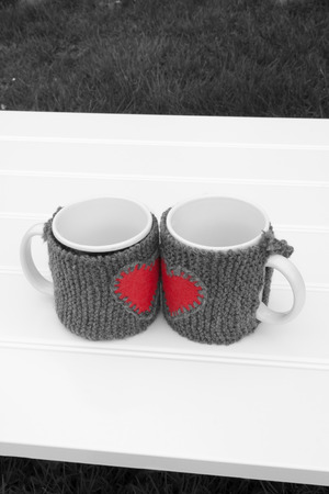 warmers: a vertical frontal black and white view of two mug with warmers creating the shape of a red heart in a white table on a garden with space for a message