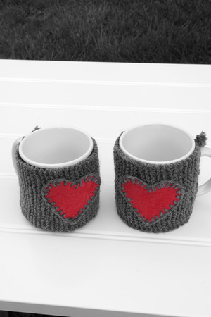 warmer: a vertical frontal black and white view of two mug with a warmer with a red heart on a table in a garden with space for a message