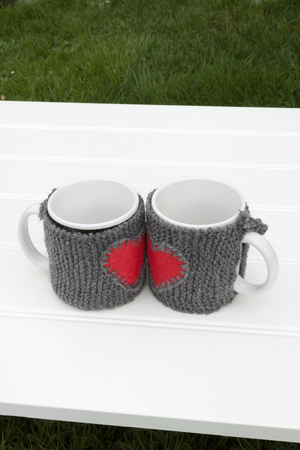 warmers: a vertical frontal view of two mug with warmers creating the shape of a heart in a white table on a garden with space for a message Stock Photo