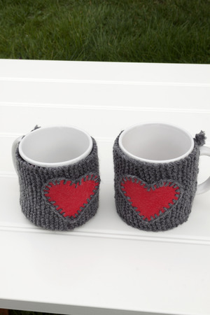 warmer: a vertical frontal view of two mug with a warmer with a heart on a table in a garden with space for a message Stock Photo