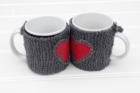 warmer: a horizontal frontal view of two mug with warmer creating a red heart shape with space for a message