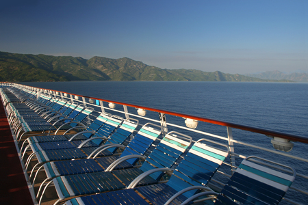 Looking over the deck of a cruise ship at the water and a Caribbean island Banco de Imagens