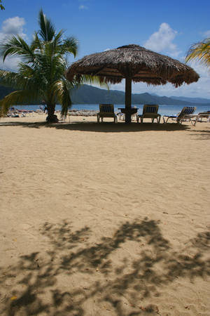 get away: Sun chairs under a thatched-roof umbrella and a palm tree on a sandy Caribbean beach