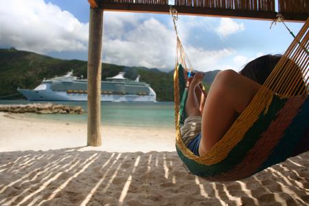 persona viajando: Una mujer se relaja en una hamaca en la playa en frente de un gran crucero
