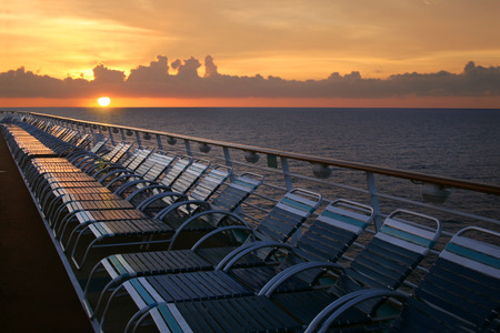 Looking over the deck of a cruise ship at sunset over the water