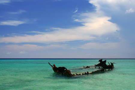 ship wreck: A rusted shipwreck sticks out of the shallow Caribbean waters Stock Photo