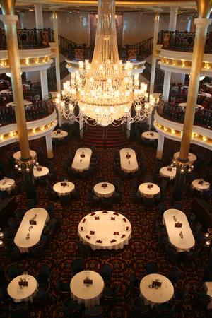 hangs: A huge chandalier hangs over tables in an elegant dining room