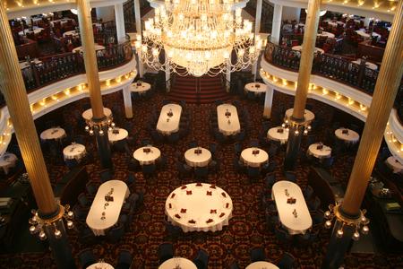 Een enorme chandalier hangt tabellen in een elegante eetzaal