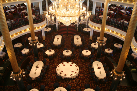 Un enorme chandalier incombe su tabelle in un elegante sala da pranzo  Archivio Fotografico - 1558431