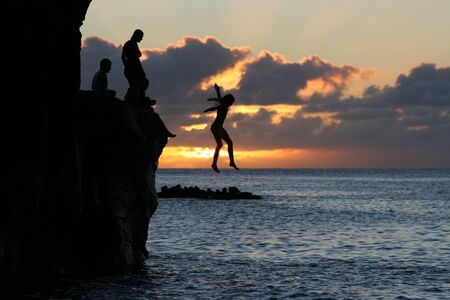 bold: Girl jump off a cliff into the ocean at Waimea Bay in Hawaii at sunset.