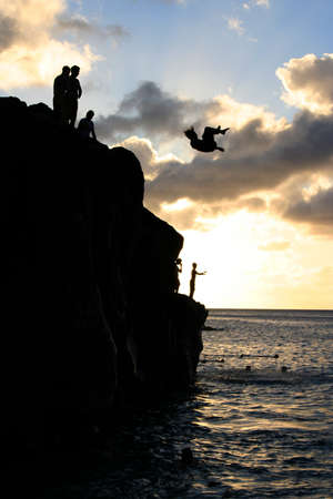 Teenage boys jump off a cliff into the ocean at Waimea Bay in Hawaii at sunset.