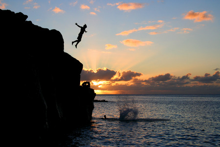 bold: Boy jumps off a cliff into the ocean at Waimea Bay in Hawaii at sunset.