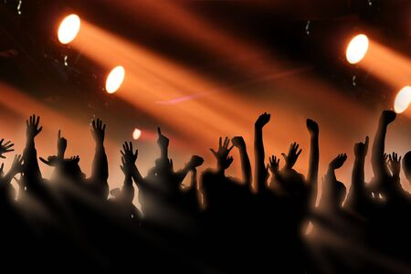 ray of light: Fans raise their hands at a concert Stock Photo