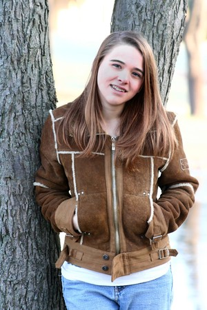 18: A teenage girl in a winter coat leans against a tree and smiles
