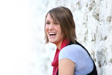 A teenage girl stands against a white rock wall and laughs photo