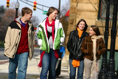 A group of fashionable young people talk and laugh, walking down a sidewalk photo