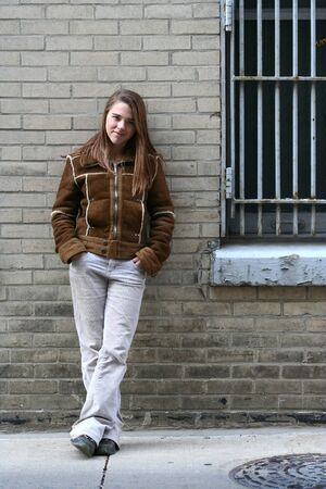 A teenage girl leans against a brick wall and smiles photo