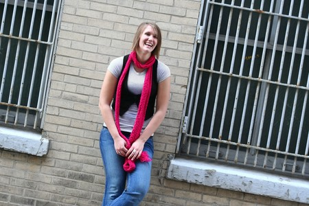 A fashionably dressed teenage girl leans against a brick wall with and laughs photo