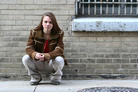 Elegantemente vestida adolescente en cuclillas contra una pared de ladrillo Foto de archivo - 3989702