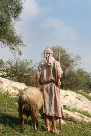 A shepherd in traditional dress leads a ram through the hills of Galilee, Israel photo