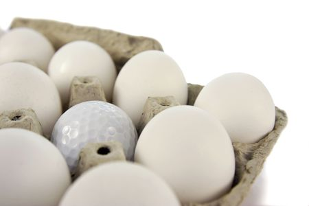 misfit: A golf ball in an egg carton over white