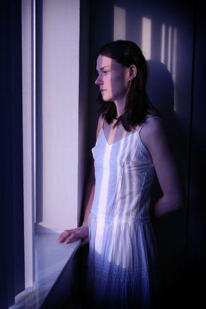 Moe, depressief zoekt vrouw kijkt uit het venster in het maanlicht Stockfoto