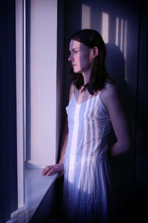 Tired, depressed looking woman stares out window in moonlight