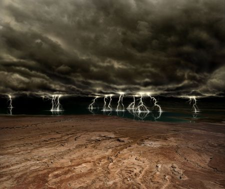 Lightning and ominous clouds over a desert plain and distant lake Stock Photo
