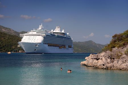 A family swims in a tropical location (Caribbean) in front of large cruise ship.
