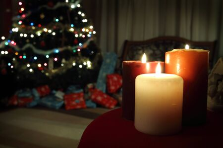 Candles burning with presents under a Christmas tree in the background
