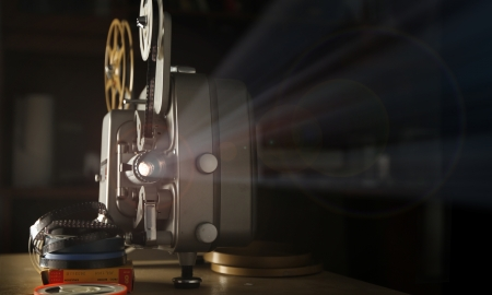 three-quarters view of a vintage 8mm film projector beaming light out, with stacks of film reels next to it.