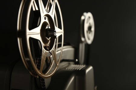 projection: Close-up of the film reels on a vintage 8mm film projector in a dark room