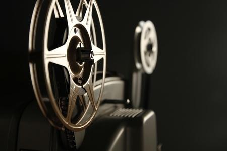 Close-up van de film rollen op een vintage 8mm film projector in een donkere kamer