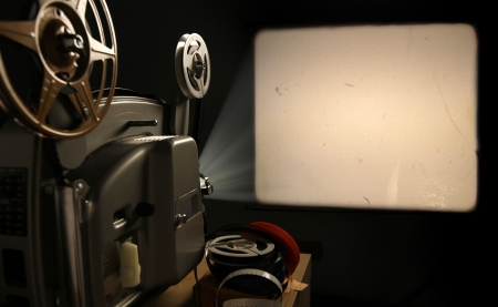 Een vintage 8mm film projector projecteert een lege afbeelding met film stof en krassen op een muur naast een stapel filmspoelen Stockfoto