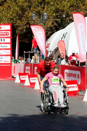 ODESSA, UKRAINE - CIRCA SEPTEMBER, 2019: Female wheel chair competitor at half-marathon in Odessa. Concept of disabled and sports. 新闻类图片