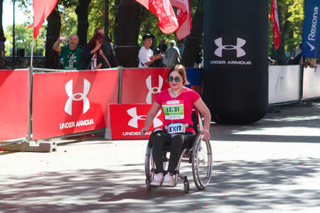 ODESSA, UKRAINE - CIRCA SEPTEMBER, 2019: Woman wheelchair competitor at half-marathon in Odessa. Concept of disabled and sports.