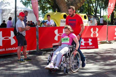 ODESSA, UKRAINE - CIRCA SEPTEMBER, 2019: Female wheelchair runner at half-marathon in Odessa. Concept of disabled and sports. 新闻类图片