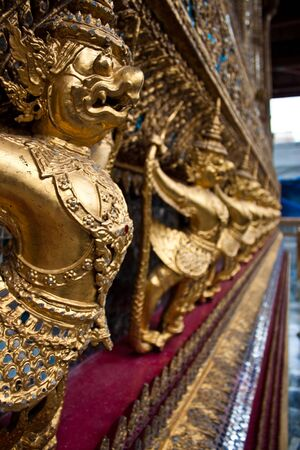 Thailand. The Grand Palace. Temple of the Emerald Buddha. Gold ornamental patter statuettes. photo