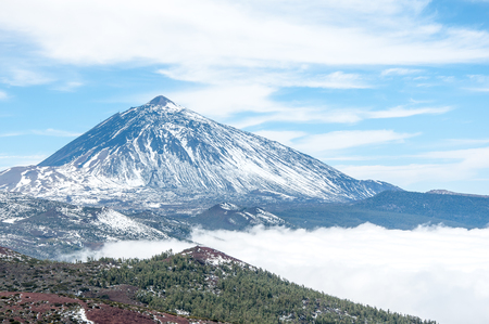 Volcanic mountain with snow and  cloudy blue sky